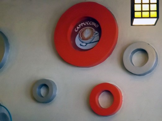 Concentric rings in silver and red decorate a wall in Cafe Deli.